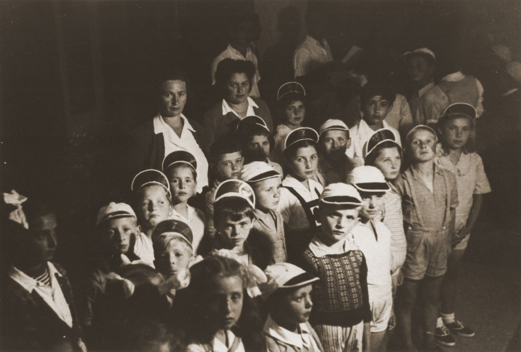 A group of Jewish DP children in the kindergarten of the Cremona displaced persons camp.  Among those pictured is Zelda Leikach (standing behind the chldren).
