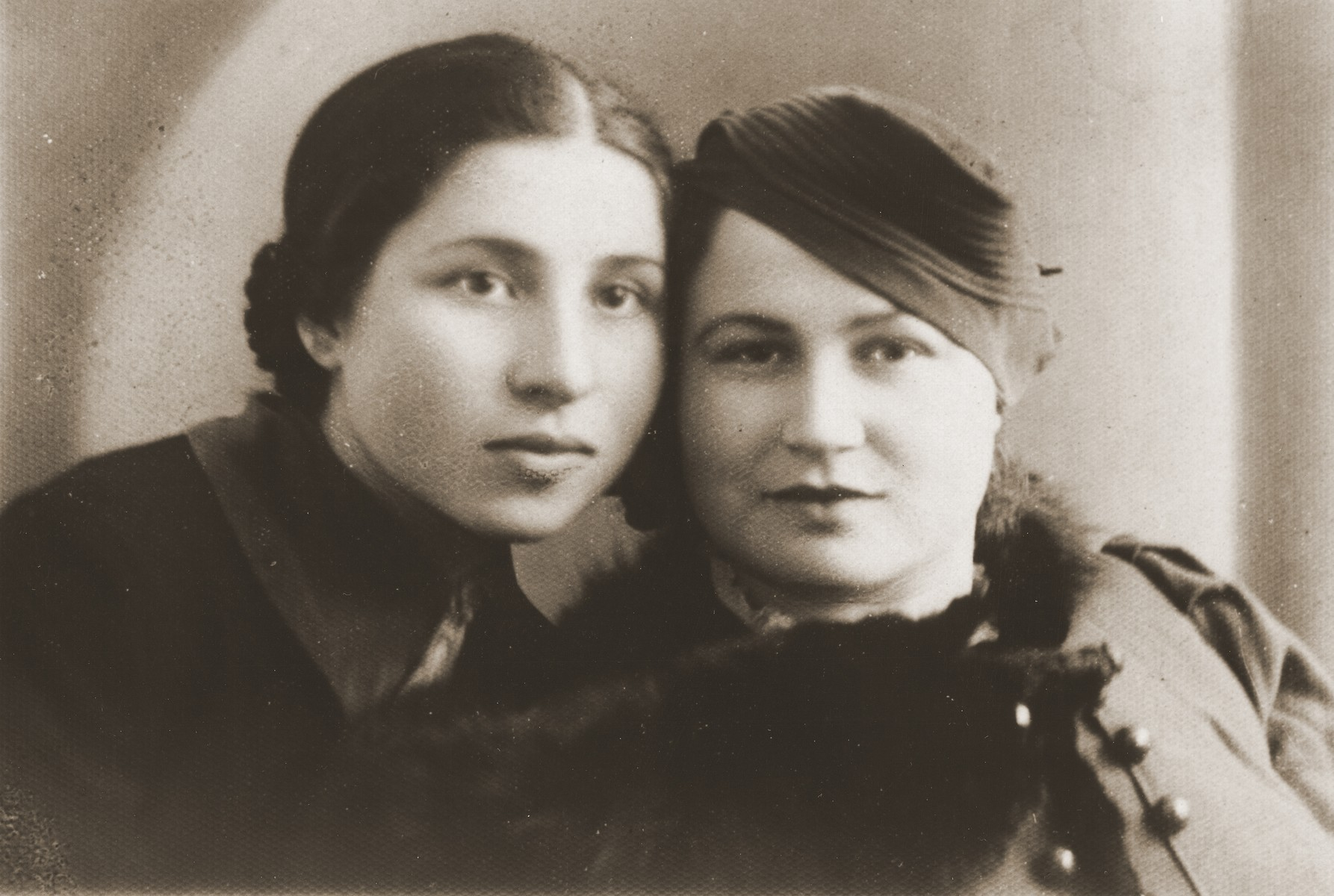 Studio portrait of two Jewish friends in Goloby, Poland.  Pictured are Lifsha Kuris and a friend.