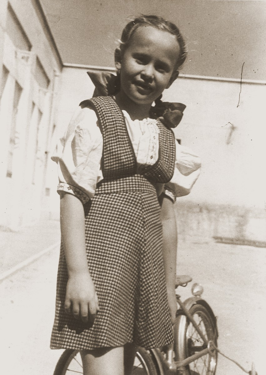 Portrait of a Jewish DP child in the Cremona displaced persons camp standing next to her bicycle.  Pictured is Masha Leikach.