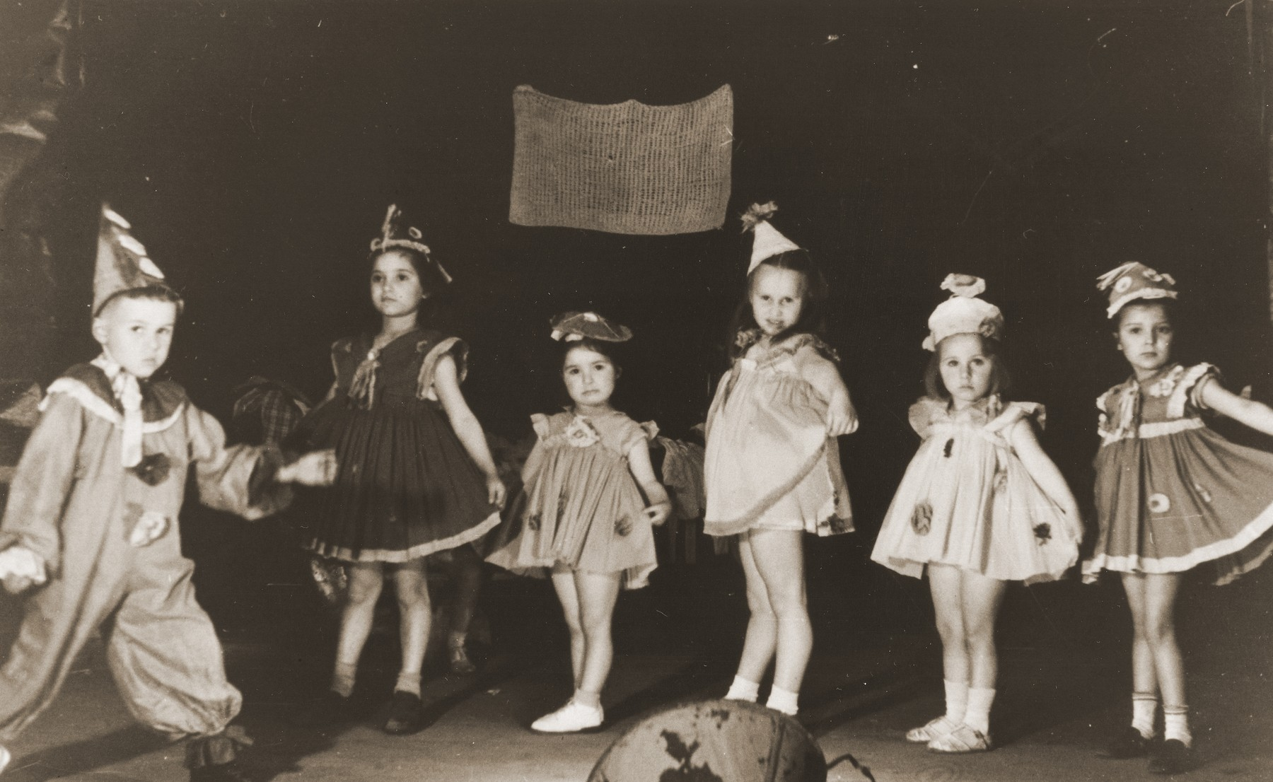 Jewish DP children take part in a Purim performance in the Cremona displaced persons camp.  Among those pictured is Masha Leikach.  Also  pictured is Shulamit Kagan (second from the right).