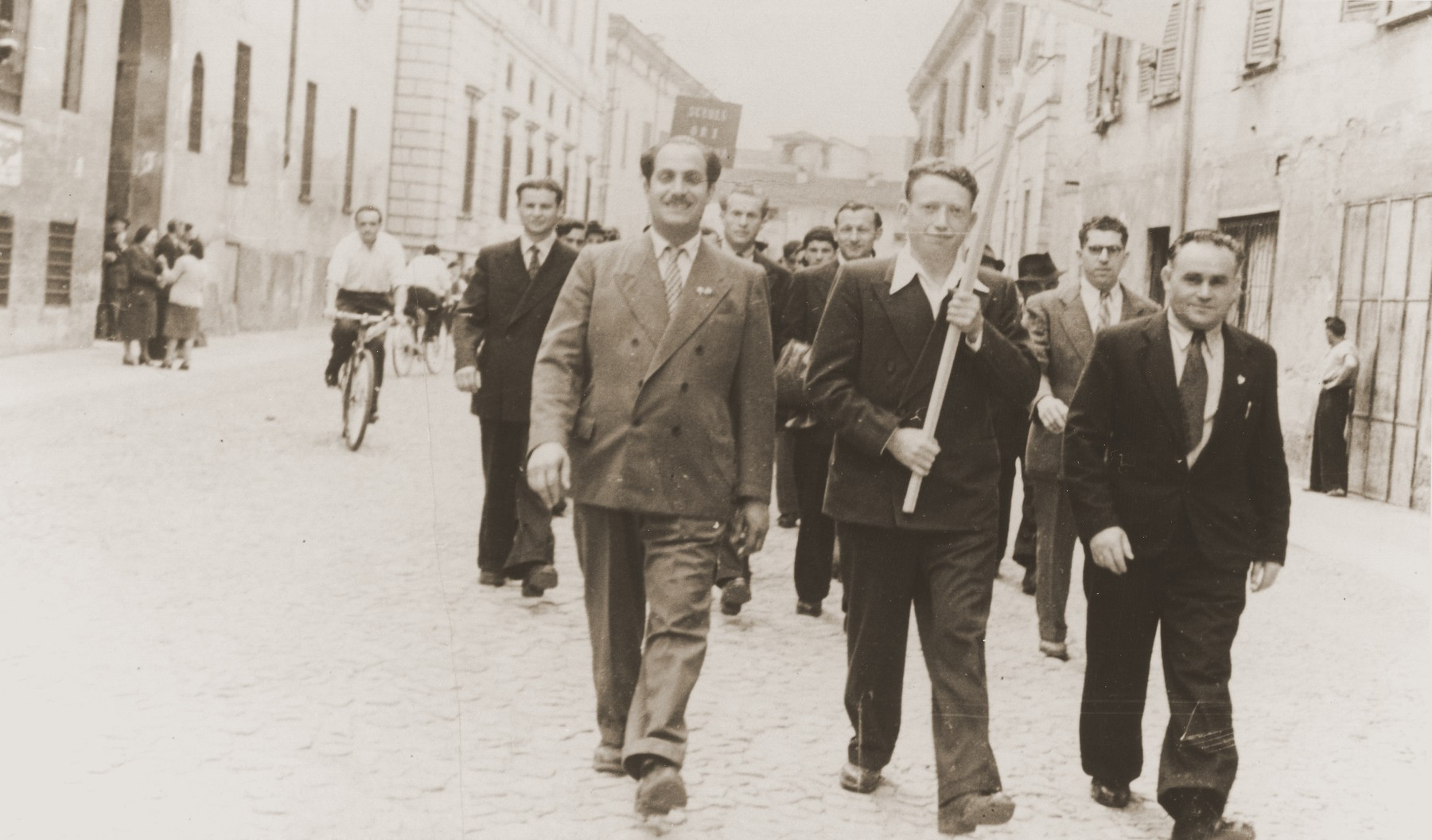 Jewish DPs in the Cremona displaced persons camp take part in a march advocating the creation of a Jewish state.    Among those pictured is Motel Leikach (front row, right).