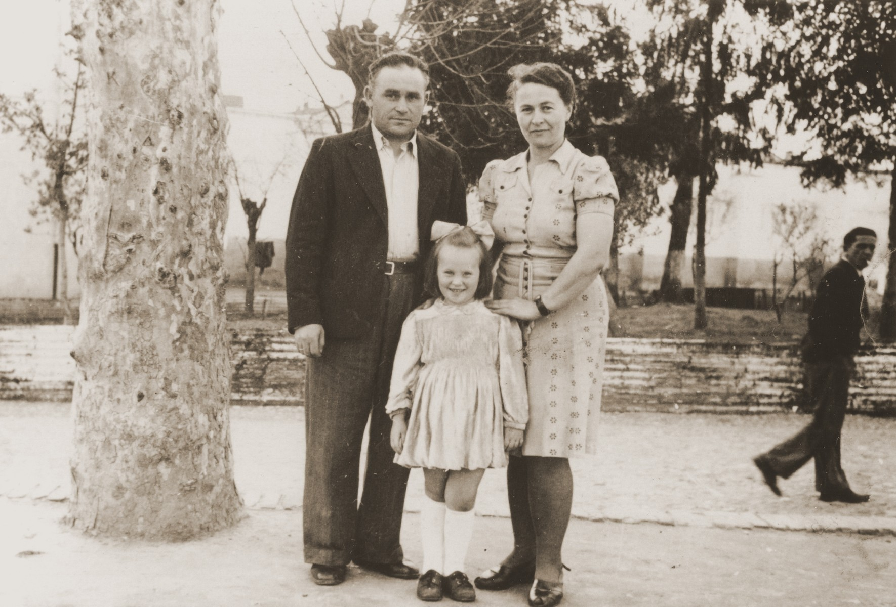 Portrait of a Jewish DP family in a park in Cremona.  Pictured are Motel, Zelda and Masha Leikach.