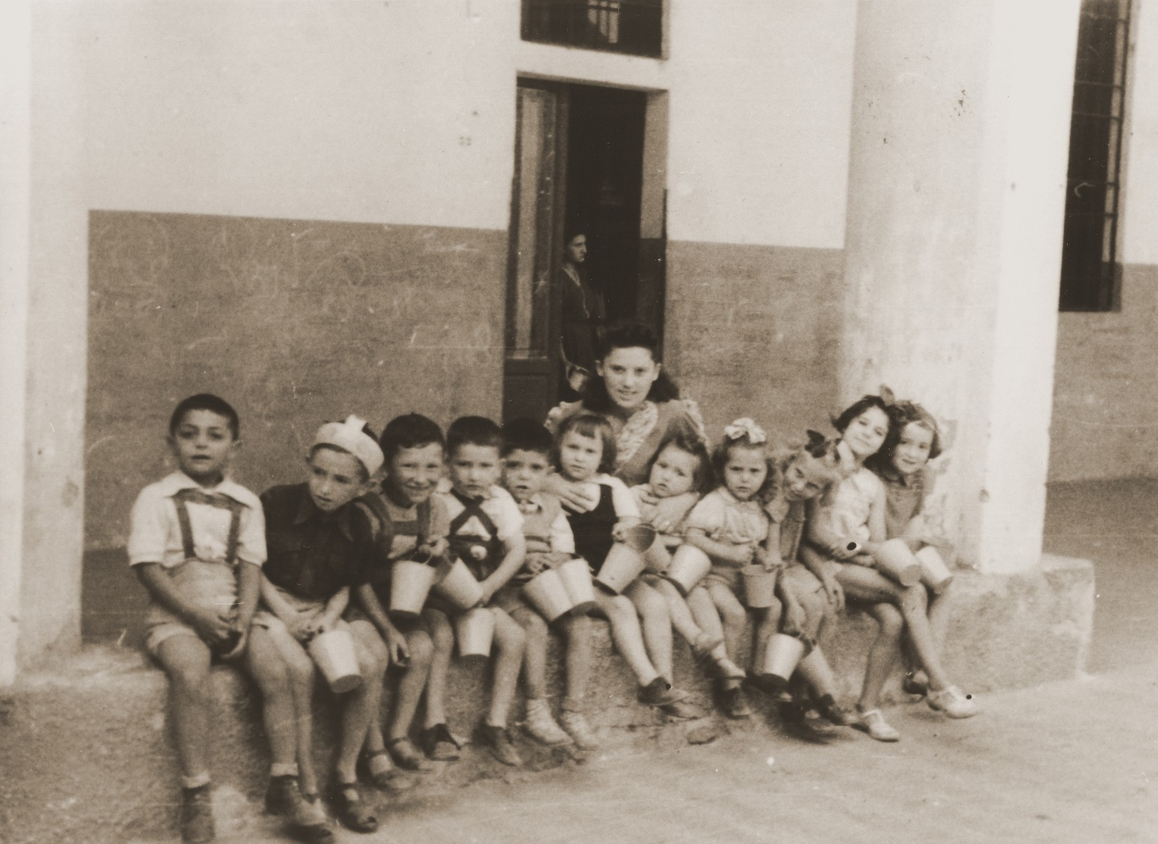 A group of Jewish DP preschool children sit outside a building in the Cremona displaced persons camp.  Among those pictured is Masha Leikach (center, to the left of the teacher).