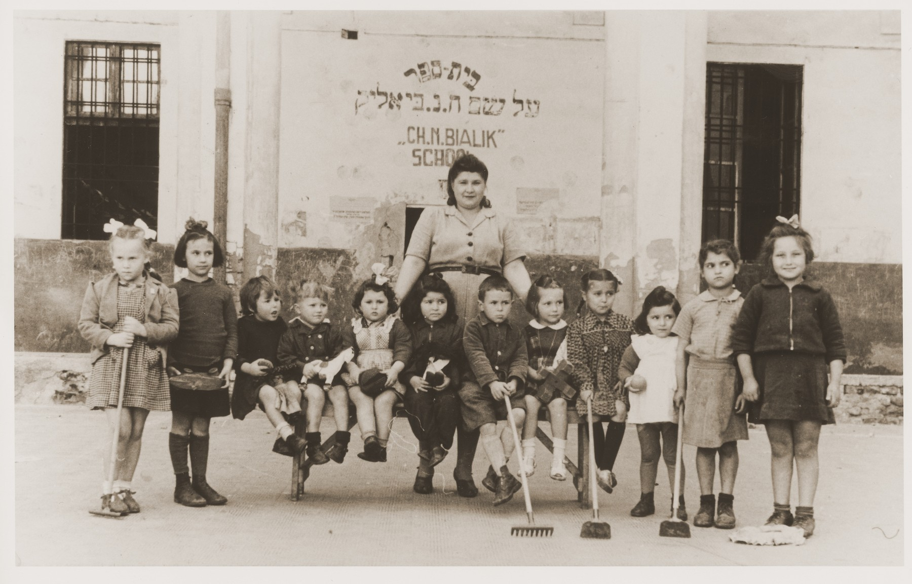 Jewish DP children at the Cremona displaced persons camp pose outside the Chaim Nachman Bialik school holding rakes and hoes.  Among those pictured is Masha Leikach (far left).
