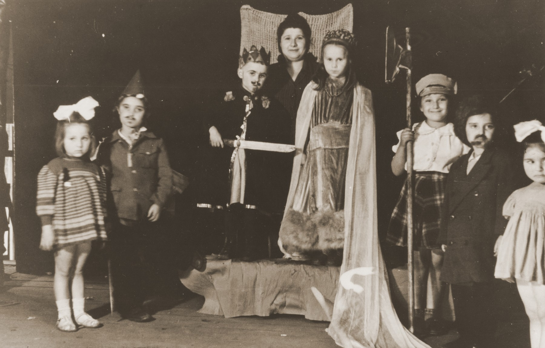 Jewish DP children perform a Purim play in the Cremona displaced persons camp.    Among those pictured is Masha  Leikach (center, dressed as Queen Esther).  Pictured on the left in the striped dress is Shulamit Gilor.