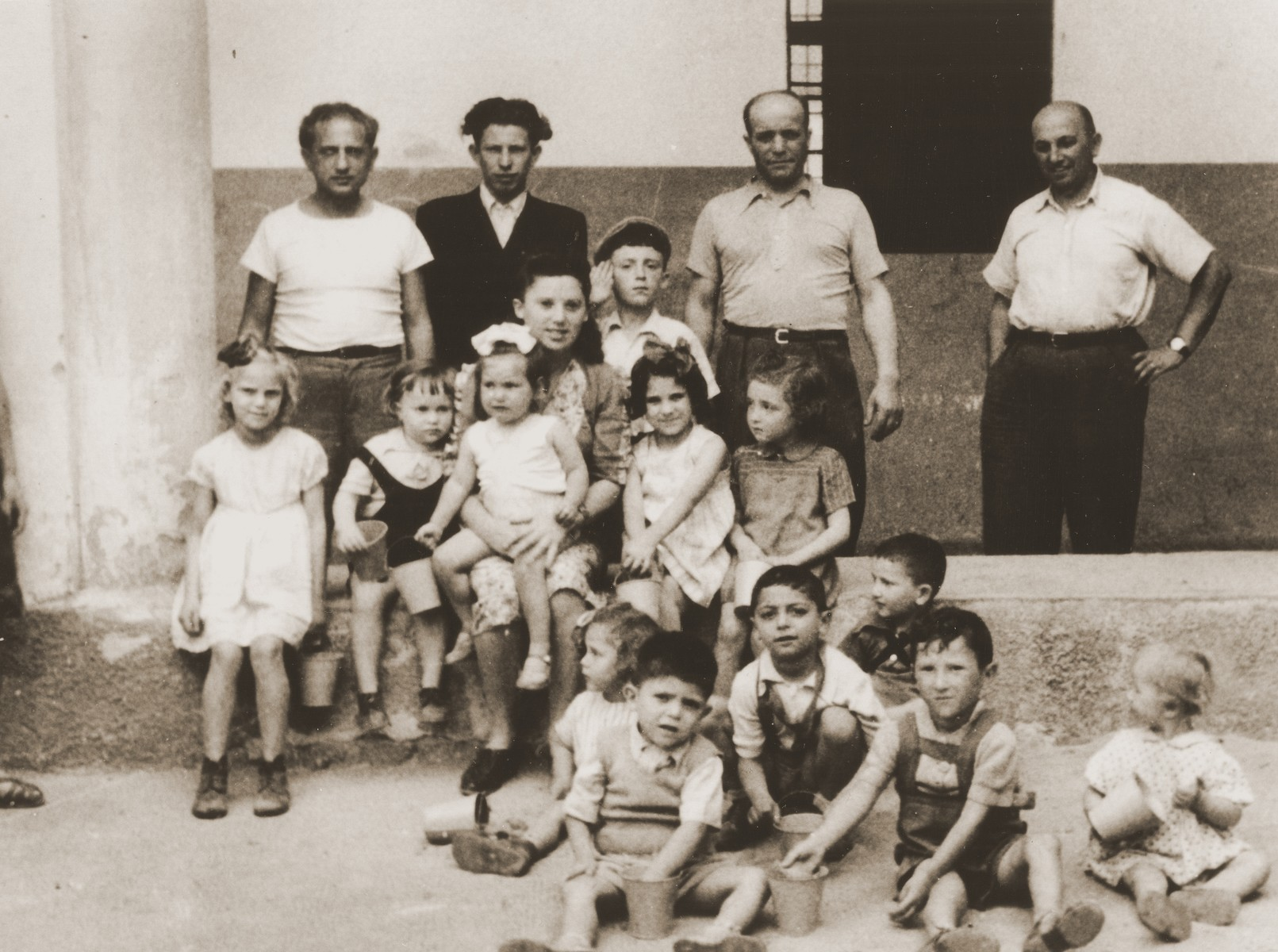 A group of Jewish DP children sit outside a building in the Cremona displaced persons camp.    Among those pictured is Masha  Leikach (seated in the middle, second from the left).