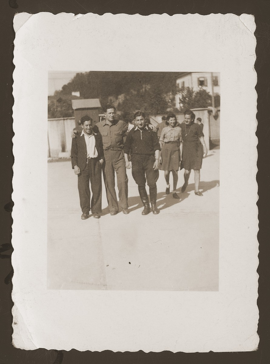 Two DP friends pose outside with an American soldier in the New Palestine displaced persons camp near Salzburg.  Pictured from left to right are Szlamek Rozencwajg, the American soldier, and Moniek Rozen.