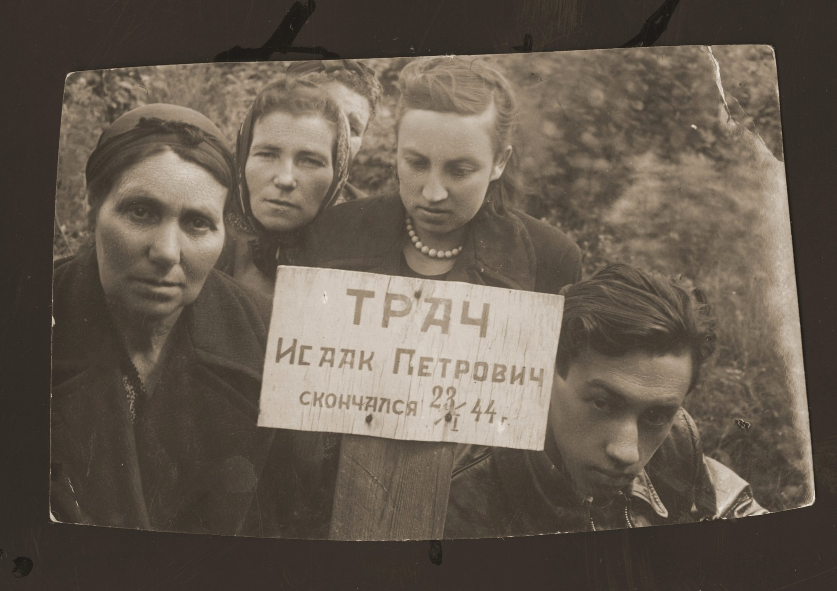 Members of the Tracz family pose at the grave of Izak Tracz, who died on January 23, 1944 in Gorky.    Estera (Ajzen) Lewin took this photograph on the eve of the family's return to Poland.