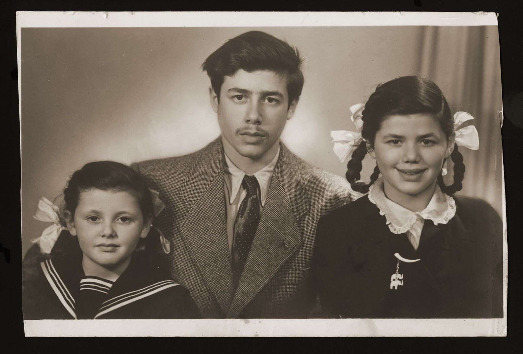 Studio portrait of three Belgian Jewish siblings who survived the war in France.    Pictured from left to right are: Josephina, Andre, and Lucie Zalc.