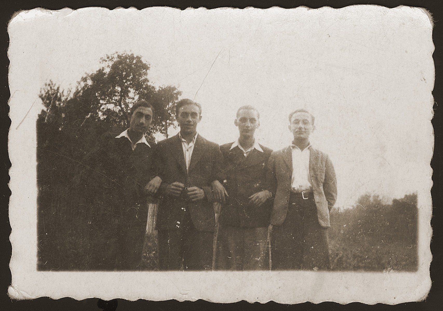 Group portrait of four childhood friends from Dabrowa Gornicza reunited in the New Palestine displaced camp near Salzburg.   Standing from left to are: Moniek Rozen, Szlamek Rozencwajg, Jakub Bajtner and Moniek Szeps.
