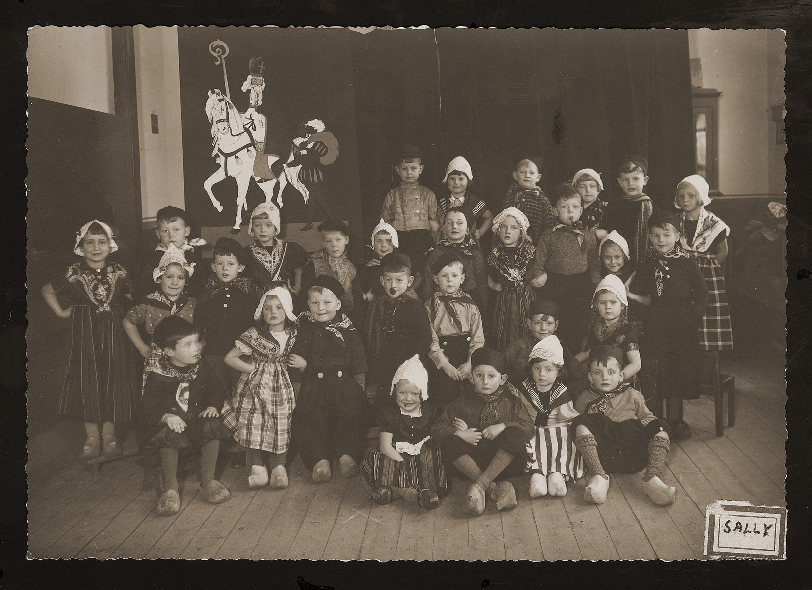 Dutch children pose in traditional costume for a school photo.  Included in the photo are a few Jewish children in hiding.