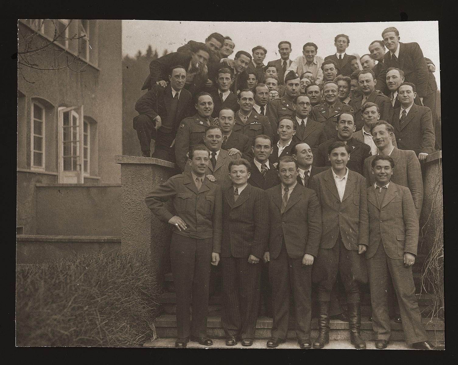 Group portrait of Jewish DPs and American soldiers at the Heidenheim displaced persons camp. Leon Kliot (Klott) is standing on the far right, third from the top.