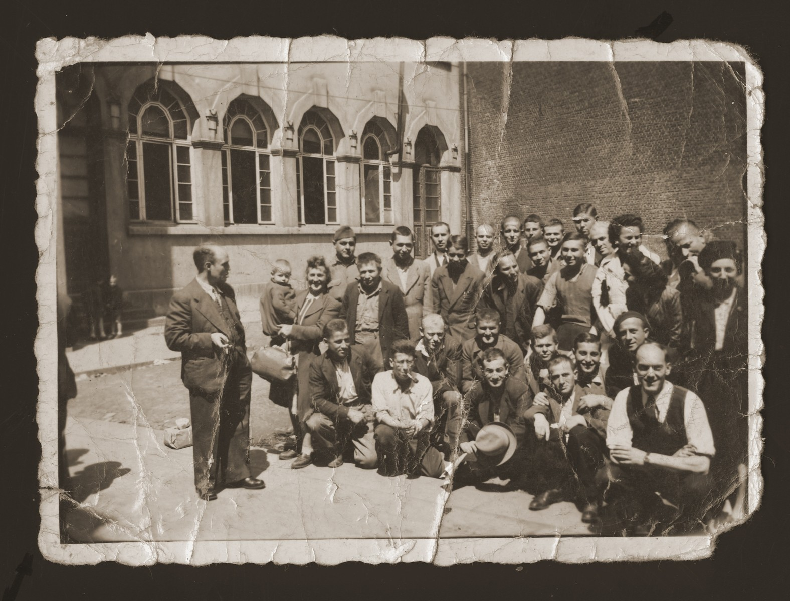 Marjana Ulman (standing, far right) and David Majer Zalc (kneeling, far right) among a group of young people posing on a street corner in Antwerp.