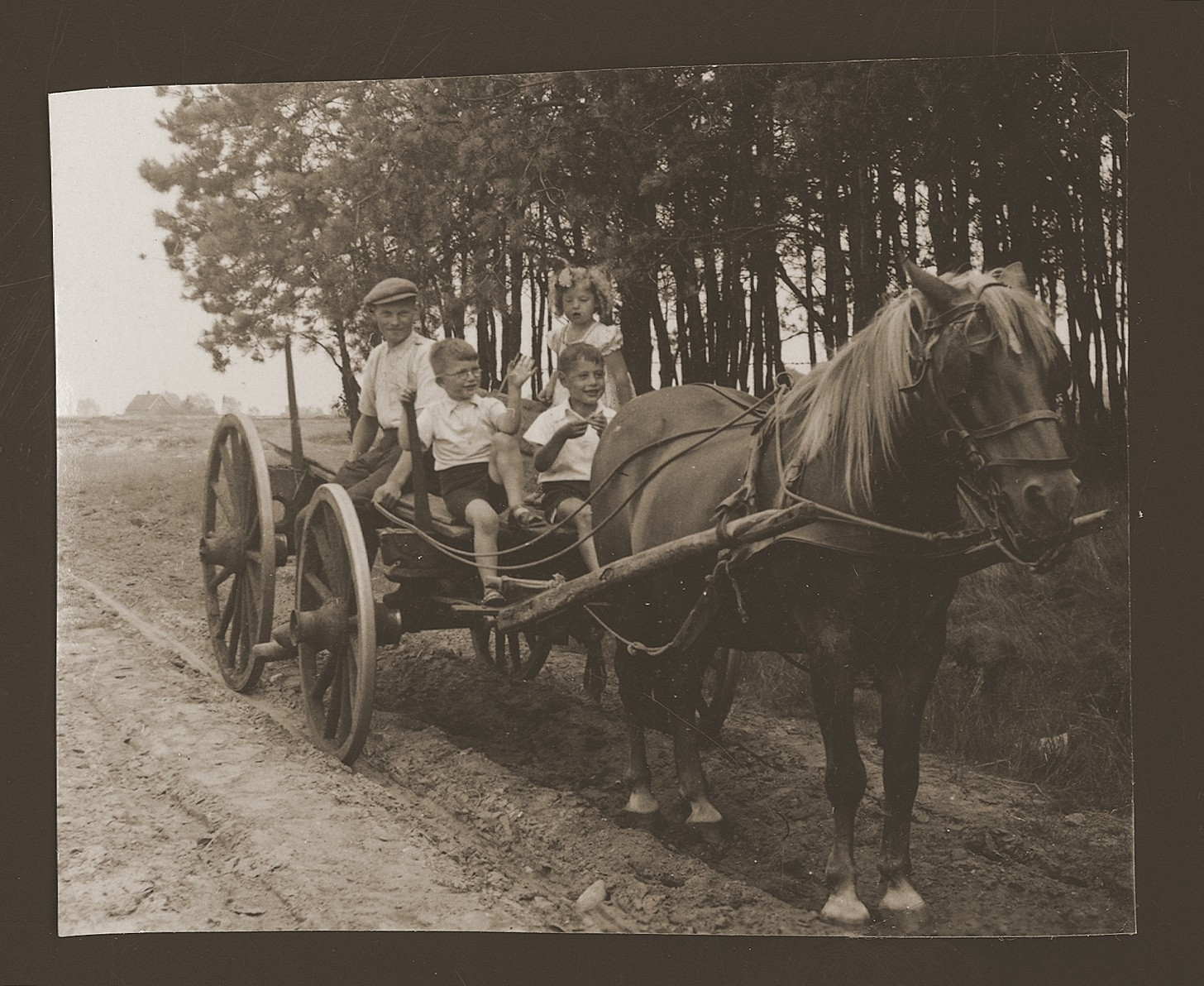 Rachel and Bernhard Kats ride on a wagon with a farmer and his son.