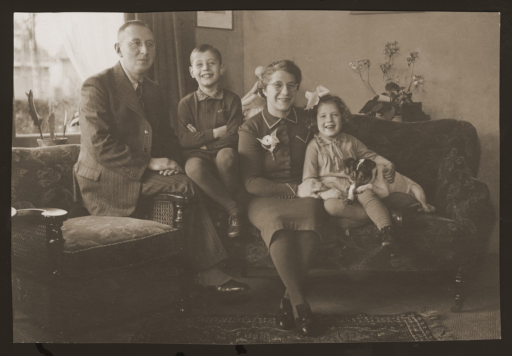 Meir and Shmuel Kats pose in their livingroom with their children Rachel and Bernhard.