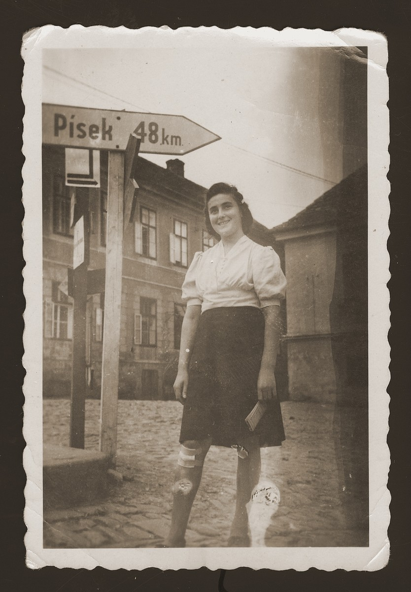 A young Jewish woman poses next to a road sign in the New Palestine displaced persons camp.  Pictured is Lilka Zylbygier.
