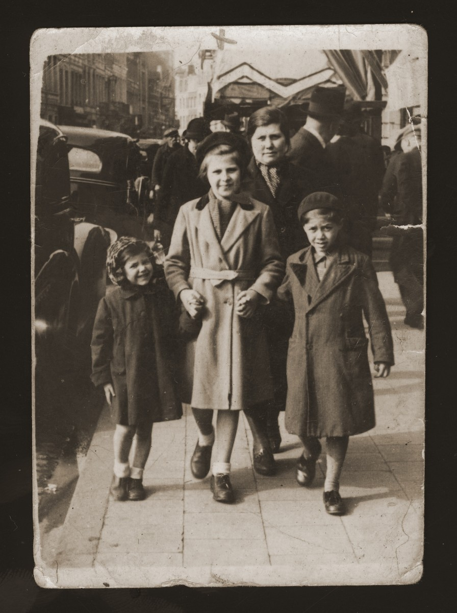 The Zalc children walk with their older cousin along a major street in Antwerp.    Pictured from left to right are: Lucie Zalc, Sara Kierschner, and Andre Zalc.  Mirjana Zalc walks behind the three children.  Sara was the daughter of Gusta Ullman and David Kierschner, the sister and brother-in-law of Mirjana Zalc.