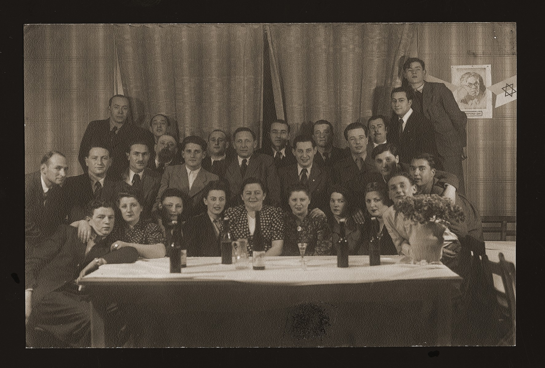 Group portrait of Jewish DPs in the Heidenheim displaced persons camp gathered around a table next to a portrait of Revisionist Zionist leader, Vladimir Jabotinsky.   Among those pictured is tanding in the second row is Leon Kliot (Klott), second from the left.  Israel Begam is fourth from the left. His wife, Esther Begam, is seated just in front of him with his hand on her shoulder.