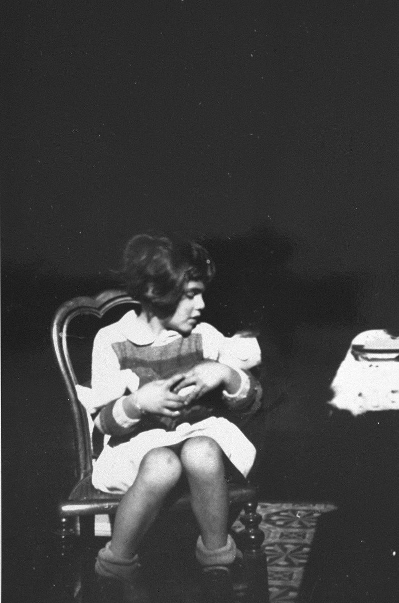 Diane Popowski, a Jewish child from Luxembourg, who was adopted by the Pallarès family after she was rescued from a nearby internment camp, sits on a chair holding a doll.