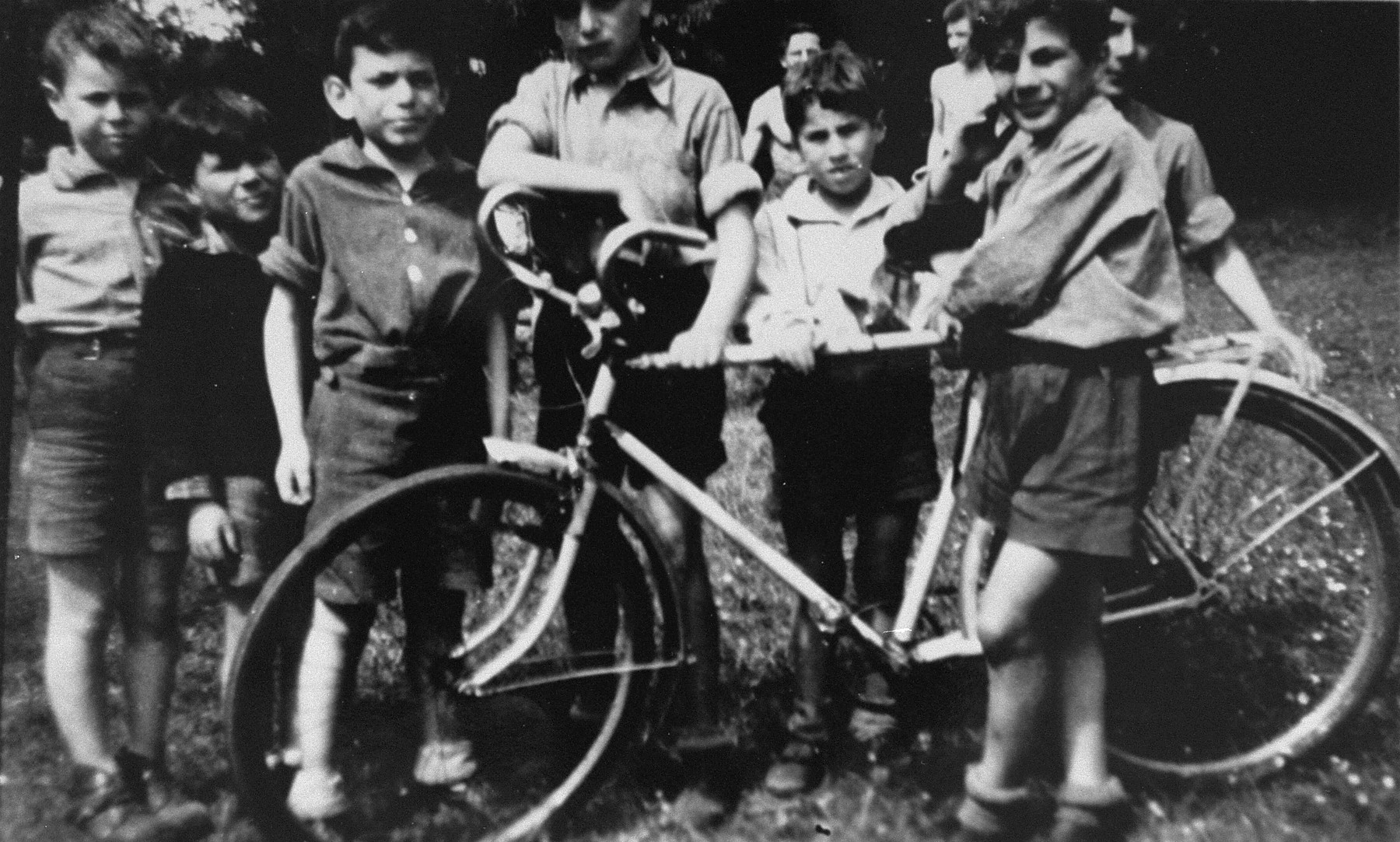 Jewish children at the OSE home in Draveil stand next to a bicycle.