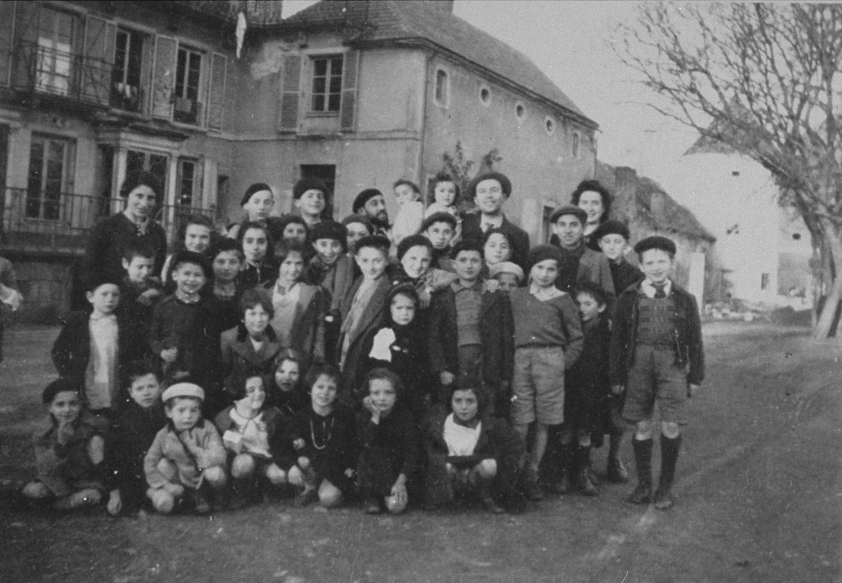 Group portrait of Jewish children outside the Château des Morelles children's home.  The home is sponsored by the OSE (Oeuvre de secours aux Enfants).    Siegfried Weissmann is pictured standing in front of the woman on the right.   Otto Herskovic is also pictured among the children.
