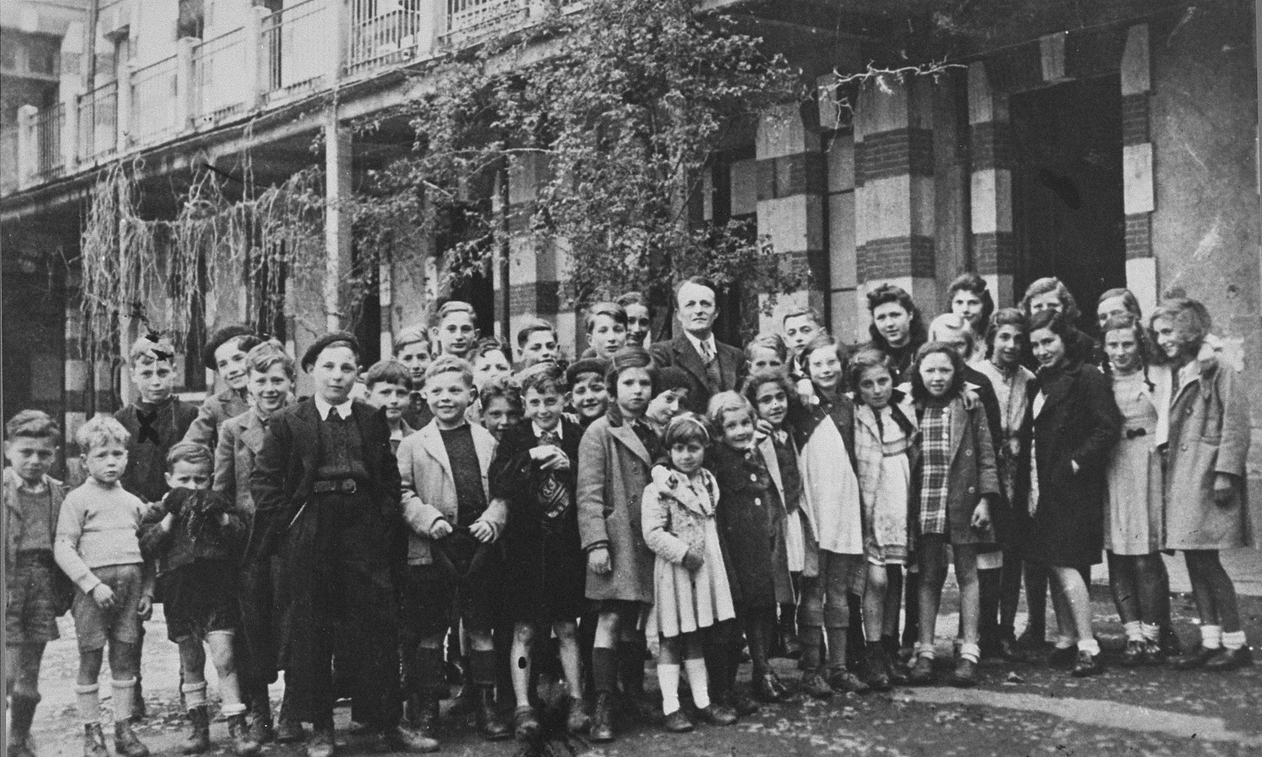 """Group portrait of Jewish children at the OSE home, """"Maison des Pupilles de la Nation,"""" in Aspet, France.    Standing in the middle of the group is the director, Henri Couvot.  Michael Oppenheimer is pictured in the last row, second from the left, his face partially hidden.    The children were brought to the home from French transit camps with the assistance of the American Friends Service Committee (AFSC) and the Oeuvre de secours aux enfants (OSE)."""