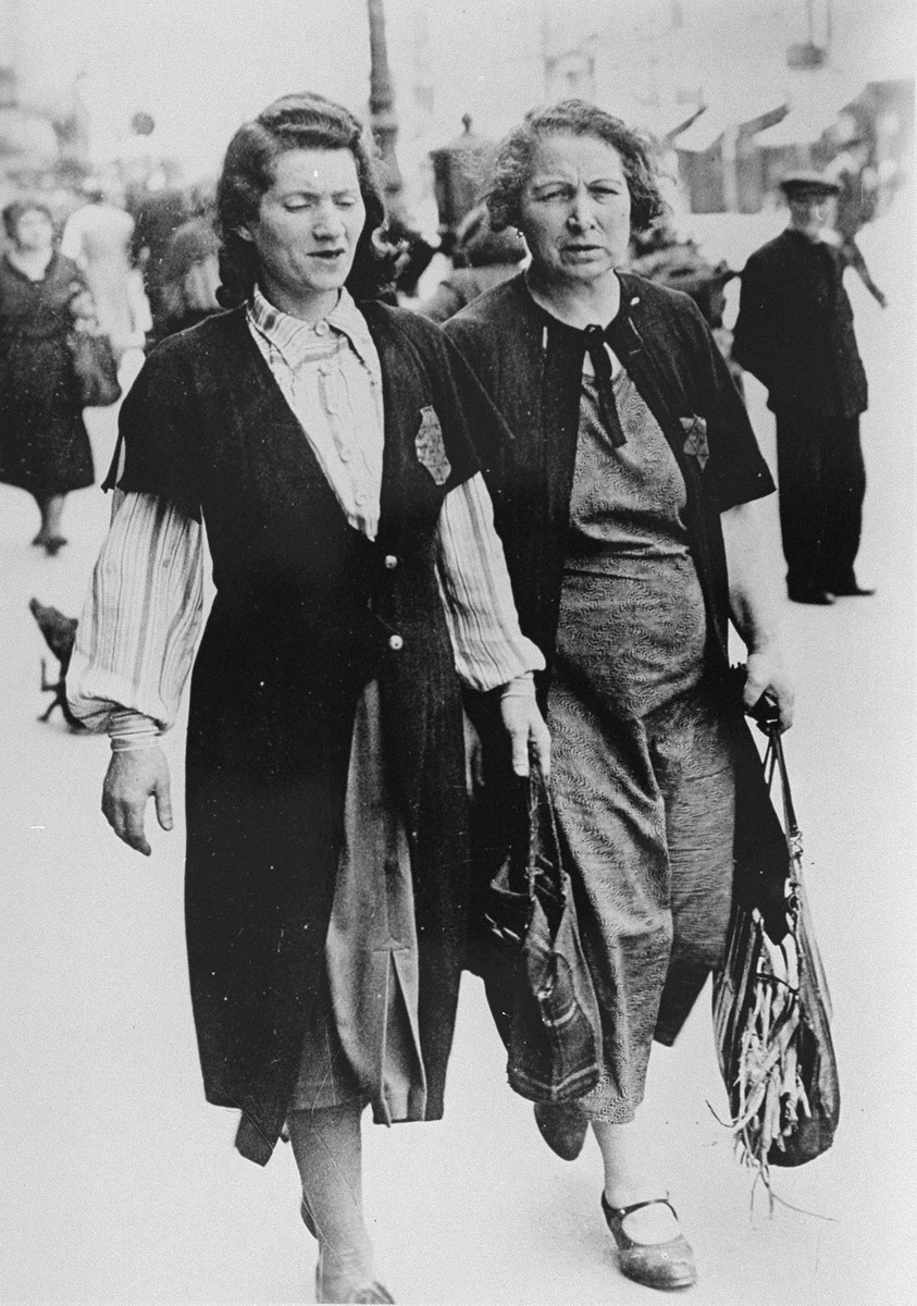 Two Jewish women, wearing Stars of David and carrying shopping bags, walk down a Paris street.