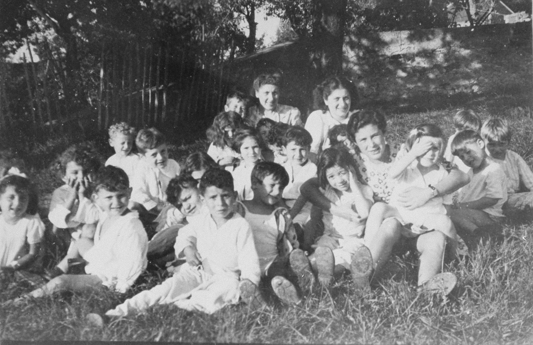 Jewish refugee children sit in the grass outside the OSE children's home in Poulouzat.