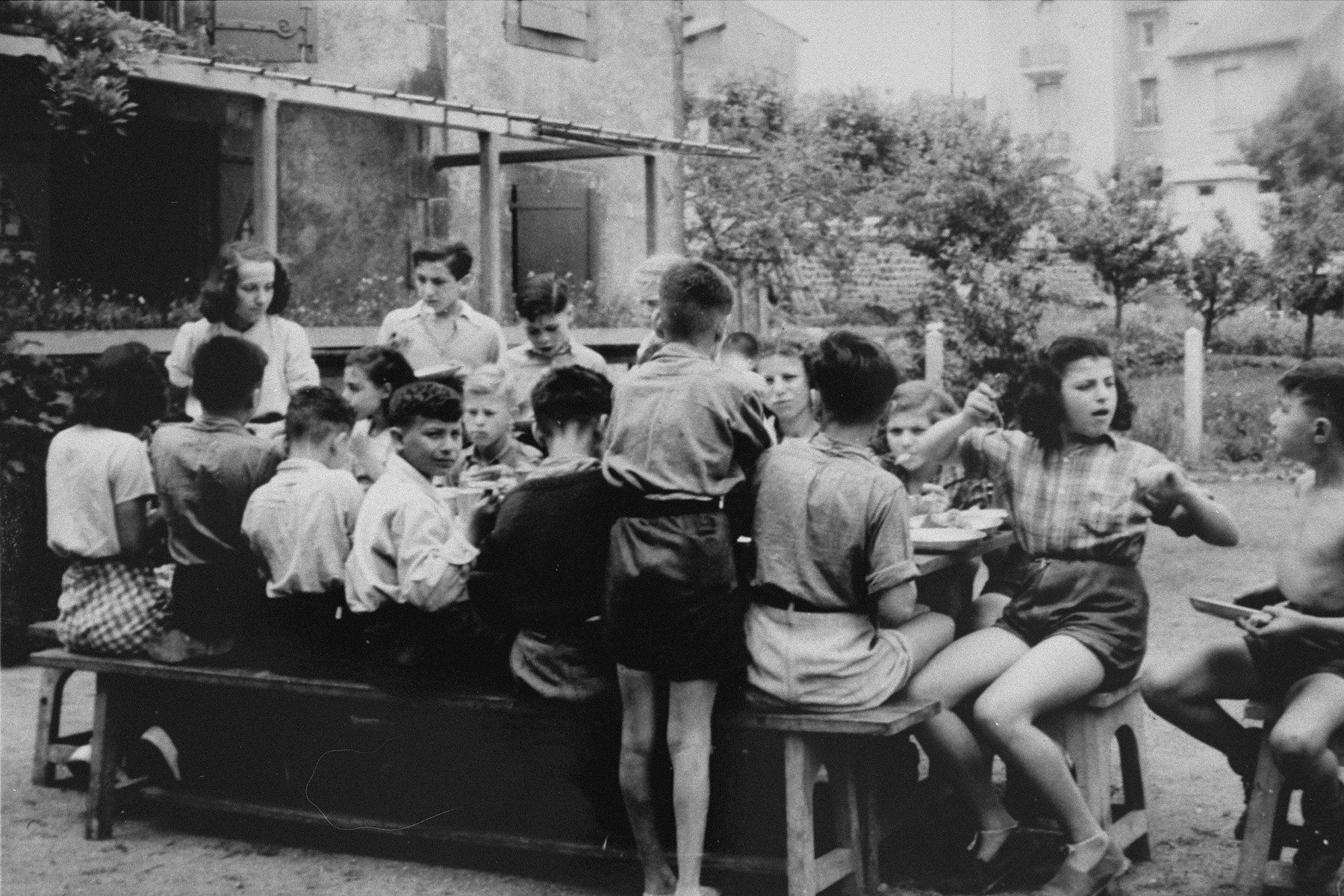 Children at an OSE home enjoy a meal outside.