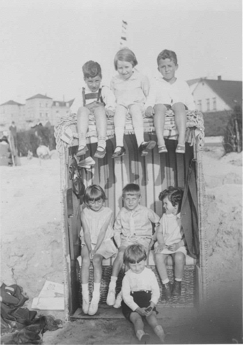 A group of children pose in a cabana on the beach in Duhnen, Germany.  Eva Rosenbaum is pictured sitting inside at the right; her brother Heinz Peter is sitting on top at the left.
