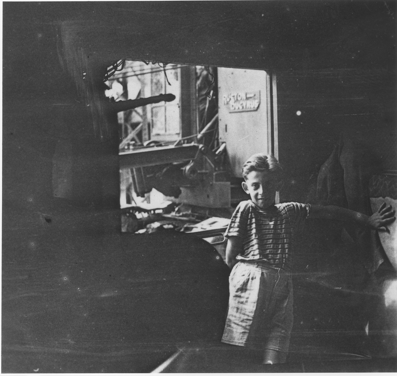 Wolfgang Schaechter poses in a garage in the Enns displaced persons camp.