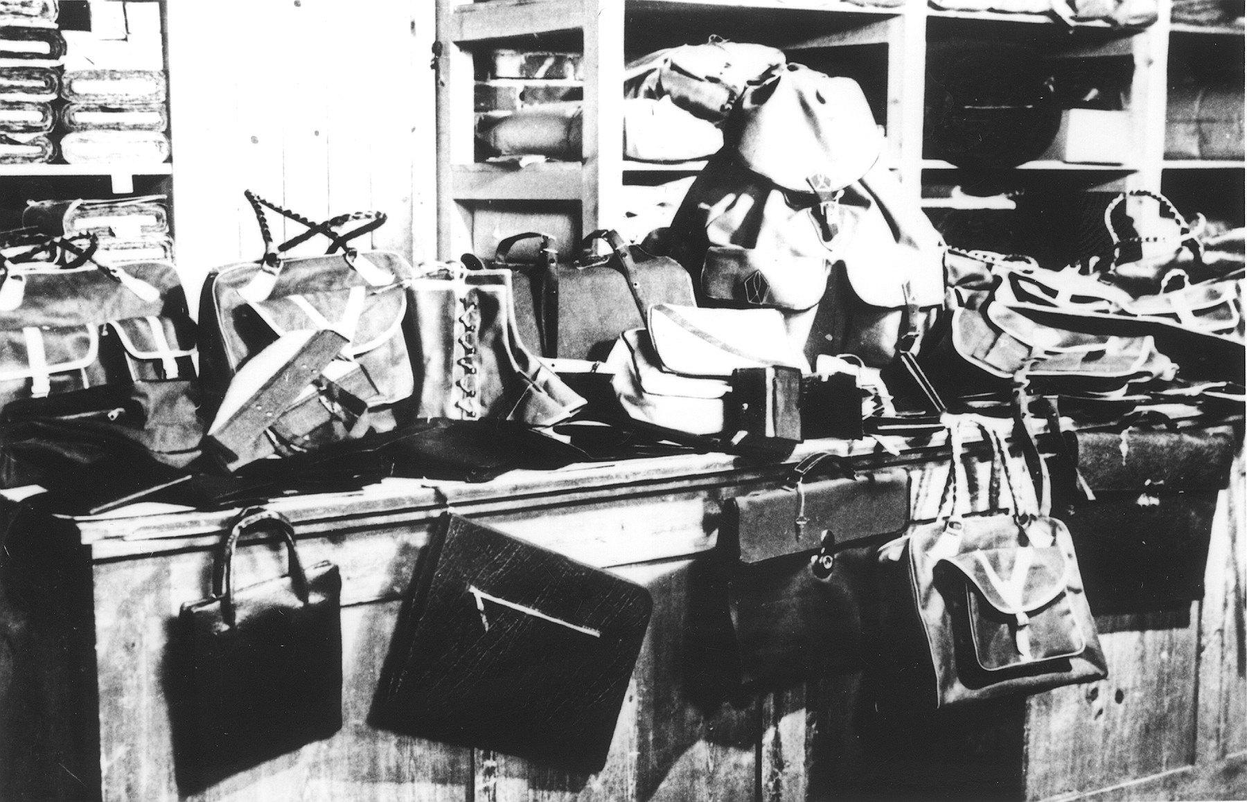 Handbags and valises made by prisoners are piled in a warehouse