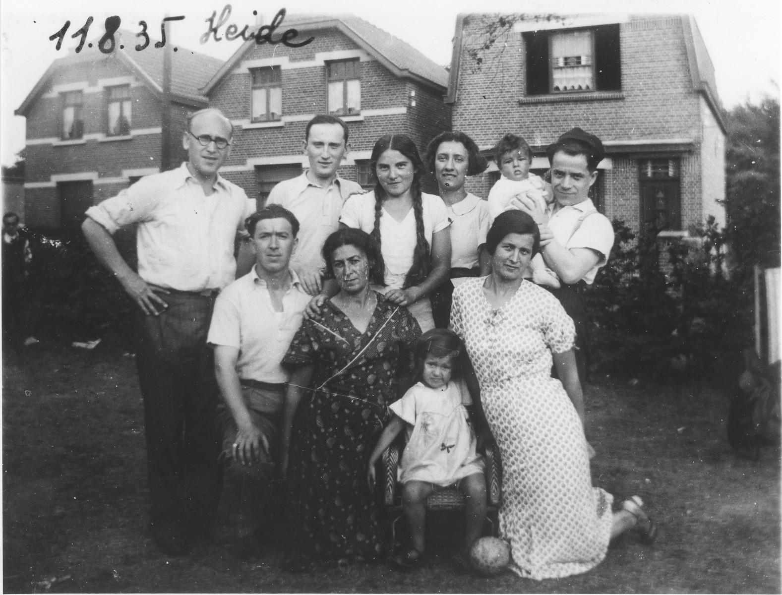Members of the Silber family pose with relatives and friends in Heide, Belgium.  Pictured in the front row from right to left are Mania Silber, Berthe Silber, Chaya Shnoni (Mania's sister) and Yoshe Meller.  In the back row at the far right, Chaim Silber holds his daughter Sara.