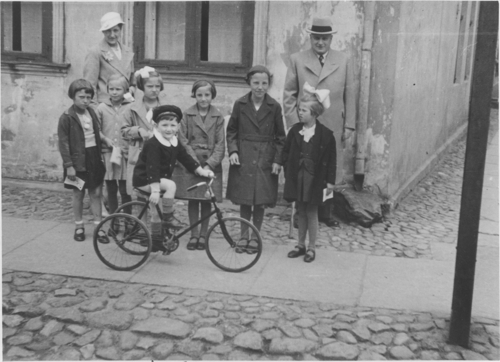 Ivar Segalowitz rides his tricycle down a street in Memel.