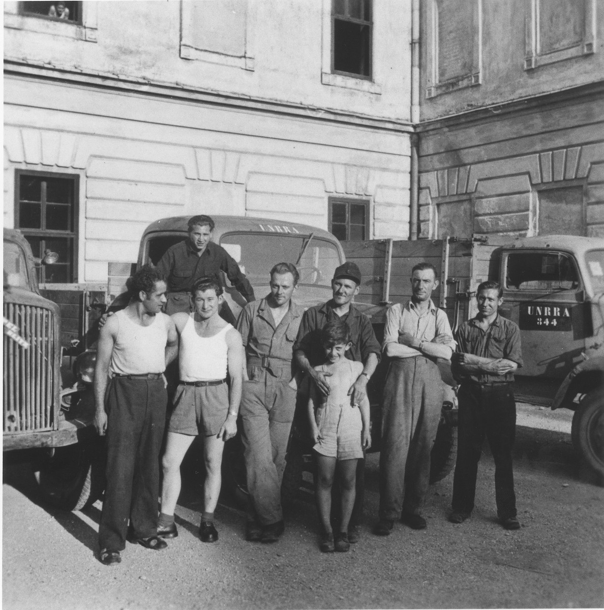 Drivers pose in front of UNRRA trucks at the Enns displaced persons camp.