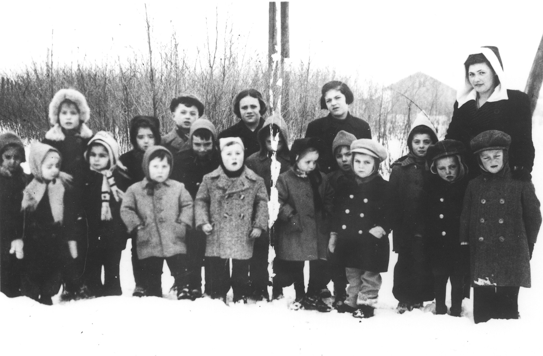 A group of young school children pose with their teacher in the Novaky labor camp.