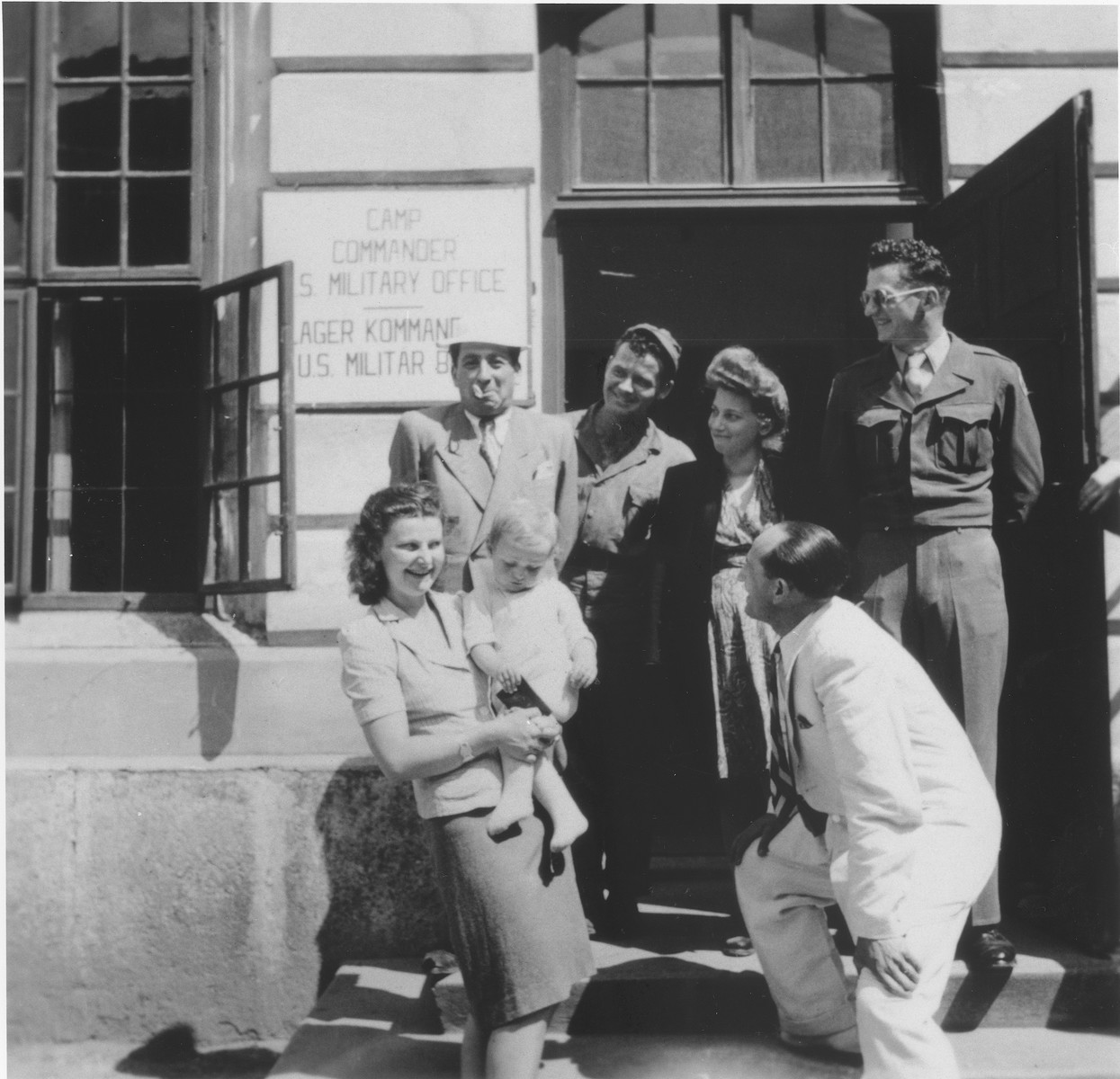 Jewish DPs are gathered at the entrance to the office of the camp commander at the Enns displaced persons camp.  Among those pictured is Alexander Schaechter (in the white suit).