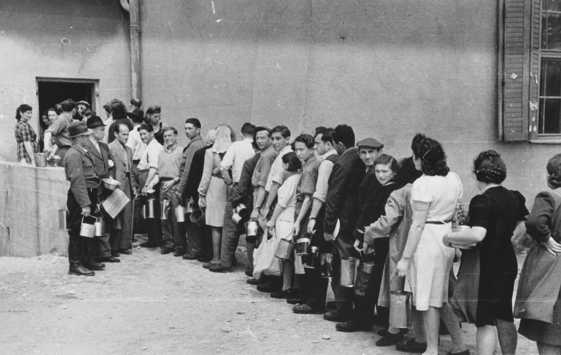 Jewish DPs carrying lunch pails wait in line outside a food distribution center in an unidentified displaced persons camp.