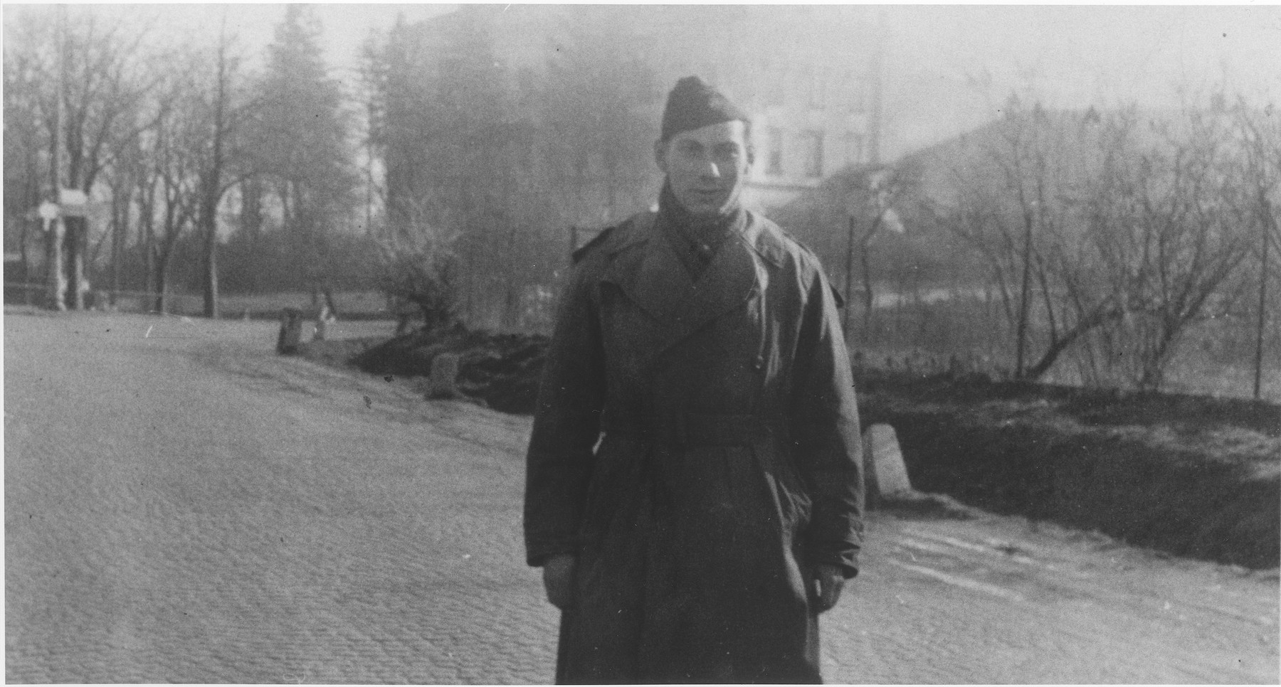 An American soldier [possibly Ltc. Nordlicht, the camp commander] poses on a street in the Enns displaced persons camp.