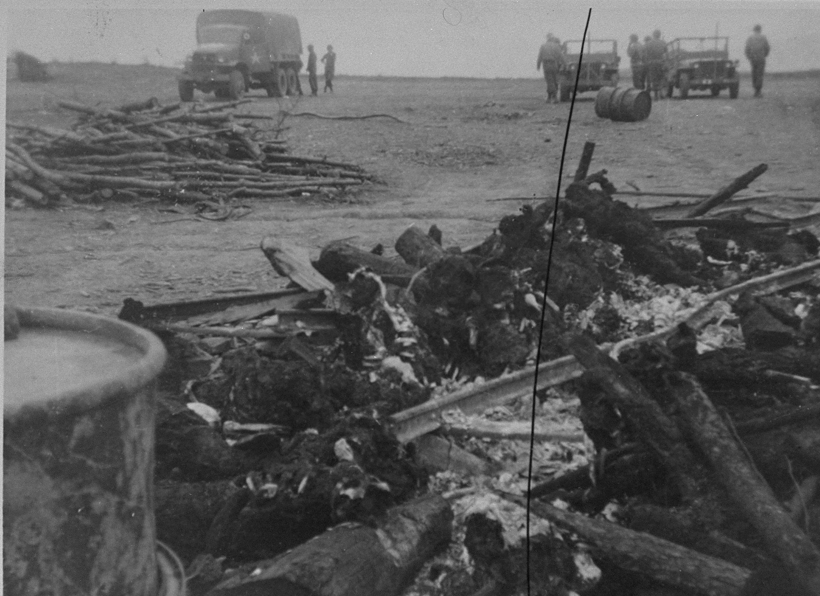 American troops and vehicles are visible behind the charred remains of prisoners' corpses, which were burned by the SS prior to evacuation of the Ohrdruf concentration camp.