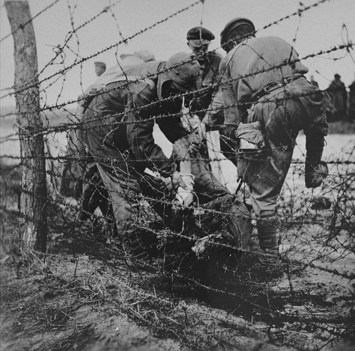 Soldiers remove corpses found in the wire of Leipzig-Thekla, a sub-camp of Buchenwald.