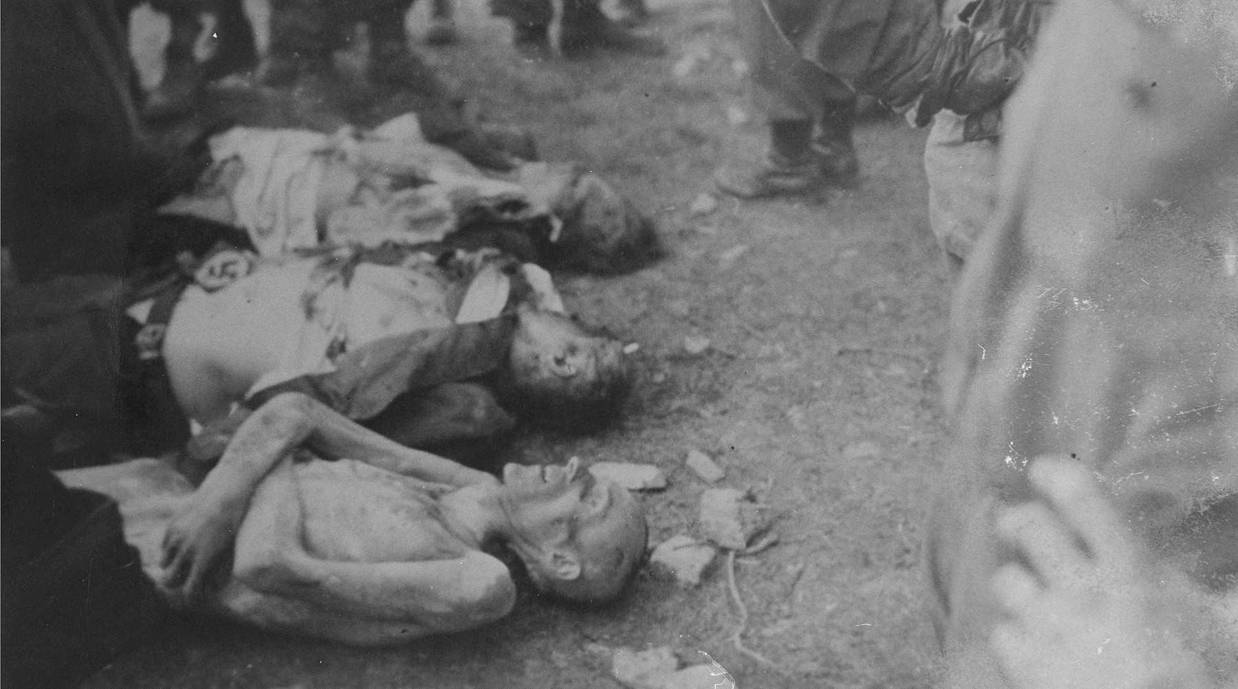 The corpse of a camp guard who was killed by survivors lies between those of prisoners who died in Ohrdruf