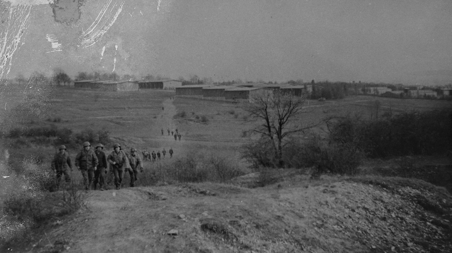 American troops walk up to the site where the dead from Ohrdruf were to be buried by German civilians.  The camp is visible in the background.