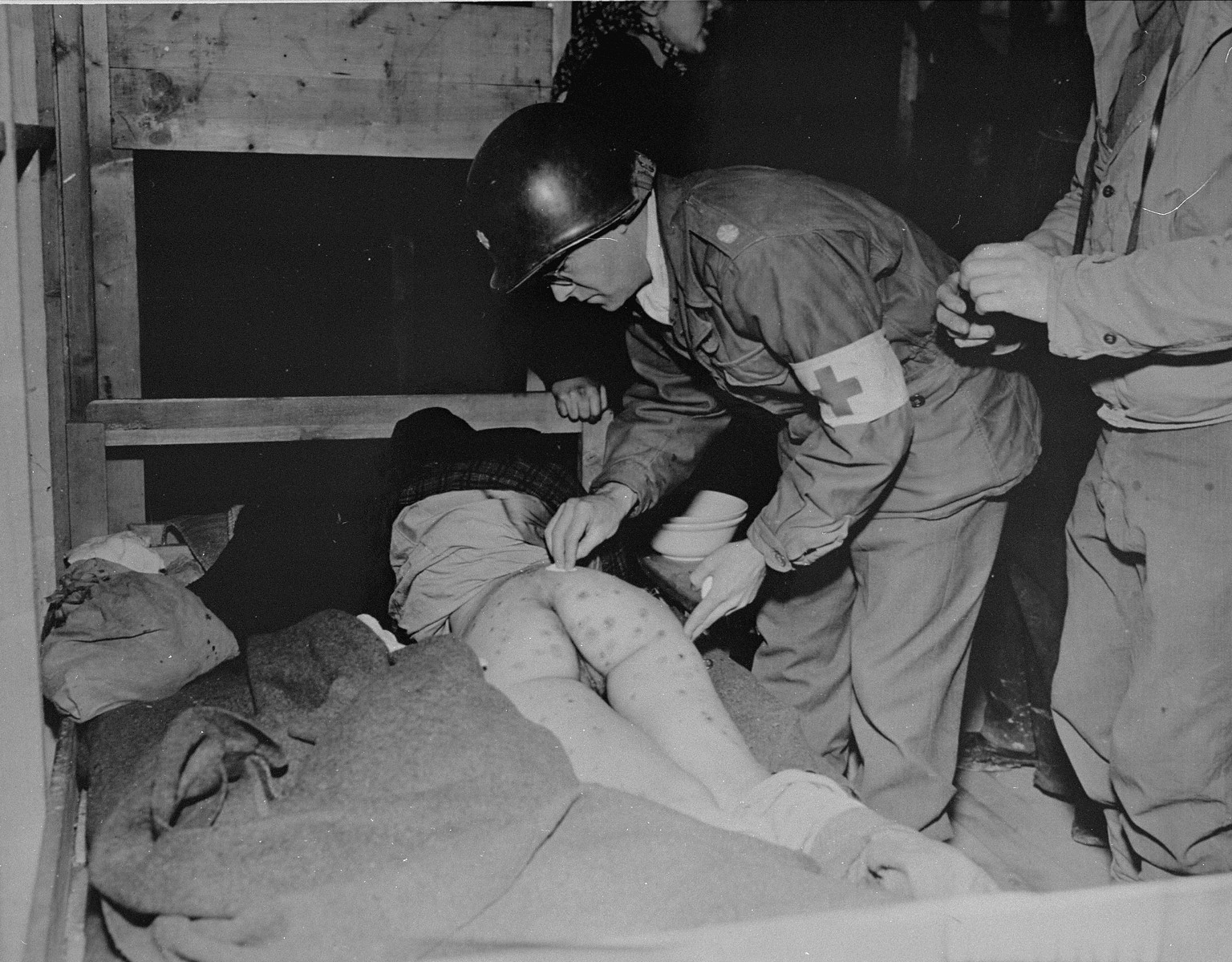 Lt. Col. J.W. Branch, Chief Surgeon of the 6th Armored Division, 3rd U.S. Army, dresses body sores of a Hungarian woman survivor in Penig, a sub-camp of Buchenwald.    Upon the approach of American troops, SS guards evacuated all those prisoners who could still walk and left behind those too ill to move.  Women in the camp suffered from starvation, typhus, diptheria, and tuberculosis.
