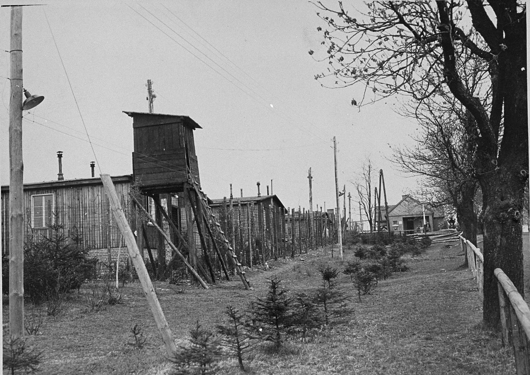 View of a section of the Ohrdruf concentration camp that includes a watchtower, barracks, and barbed wire fencing.