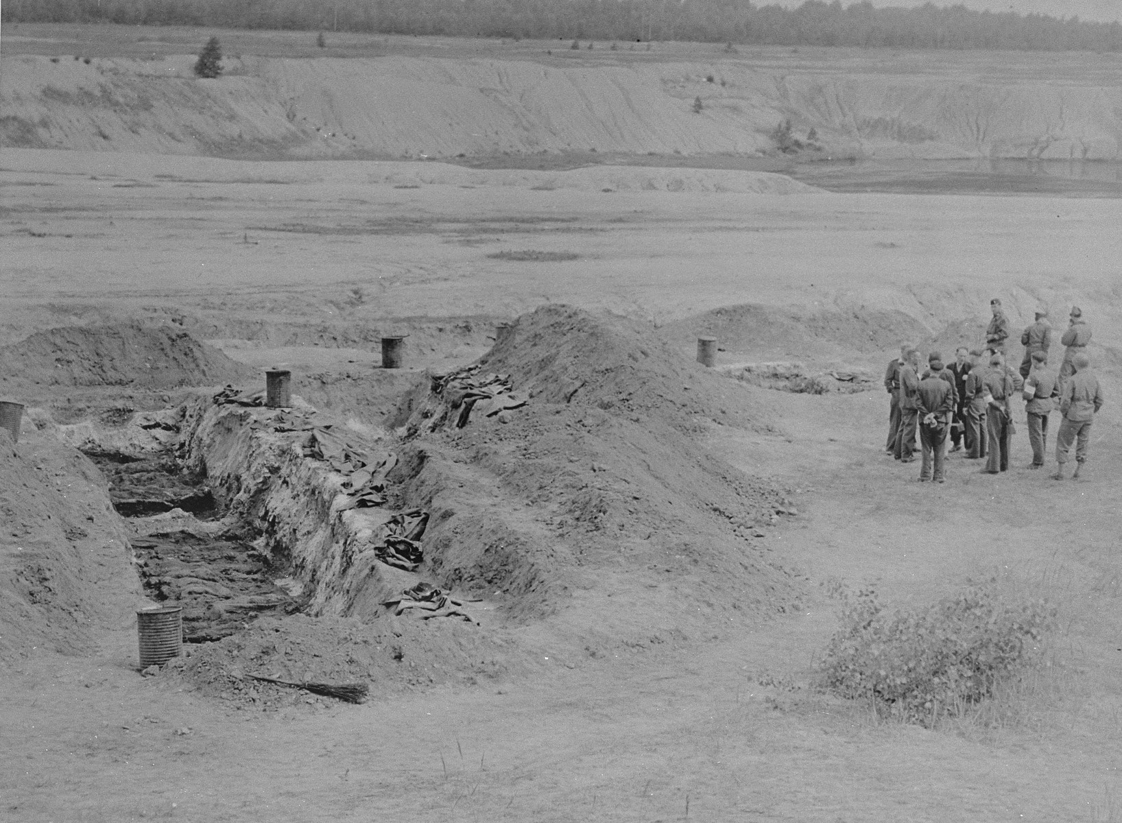 American soldiers stand near a recently exhumed mass grave in Berga-Elster, a sub-camp of Buchenwald.