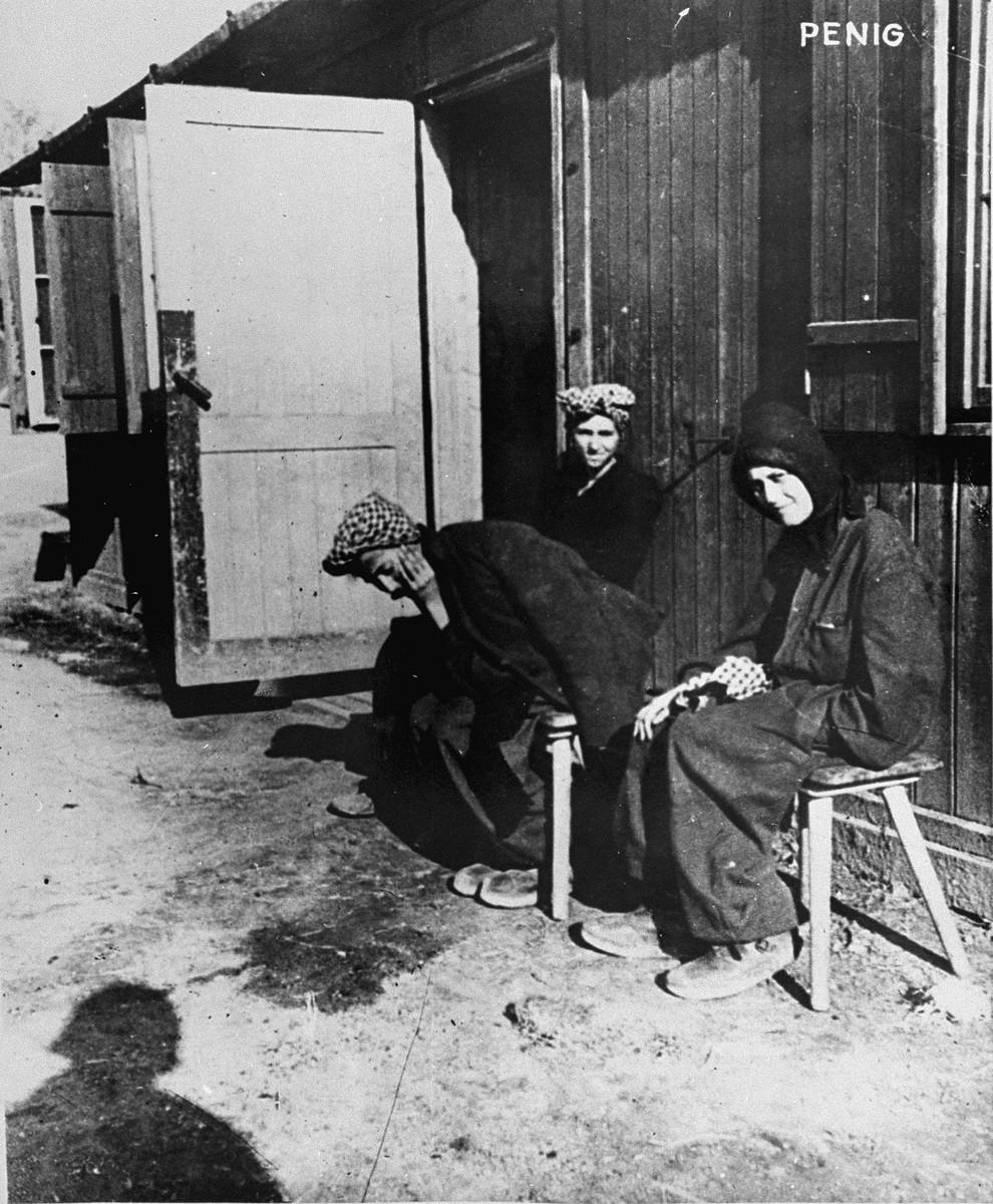 Three Hungarian-Jewish women survivors sit outside their barracks in Penig, a sub-camp of Buchenwald.