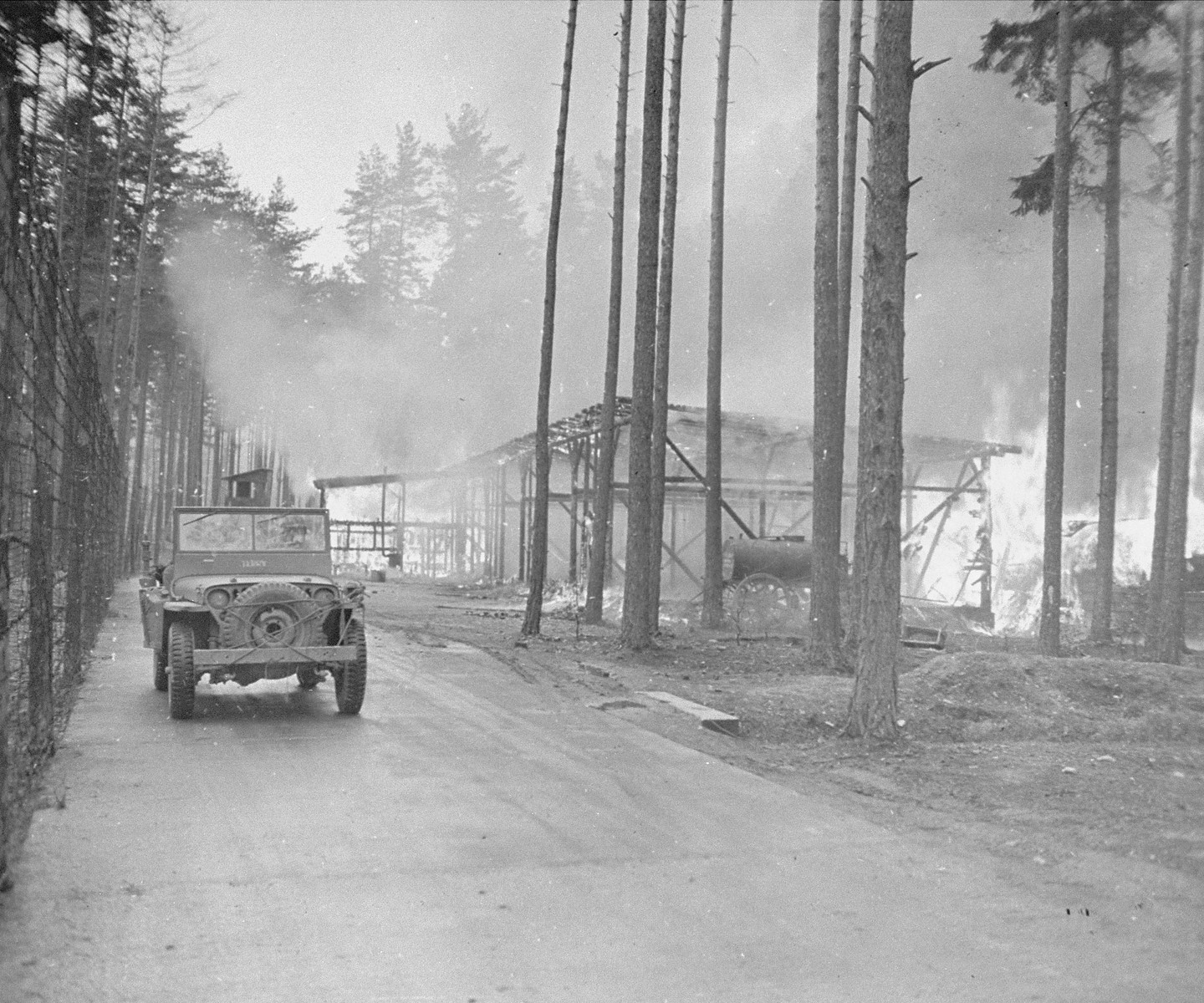 An American soldier drives past buildings set afire by survivors after the SS evacuated the Ohrdruf concentration camp.