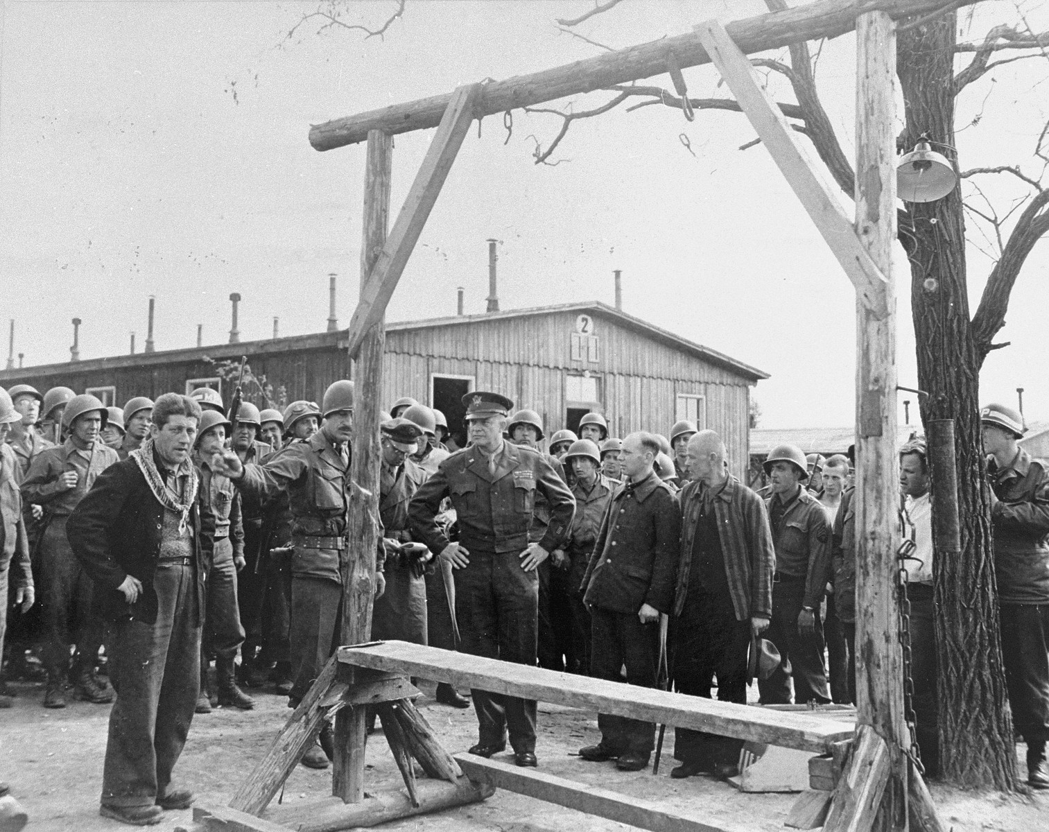 """During an official tour of the newly liberated Ohrdruf concentration camp, an Austrian Jewish survivor describes to General Dwight Eisenhower and the members of his entourage the use of the gallows in the camp.  Among those pictured is Jules Grad, correspondent for the U.S. Army newspaper """"Stars and Stripes"""" (on the right)."""