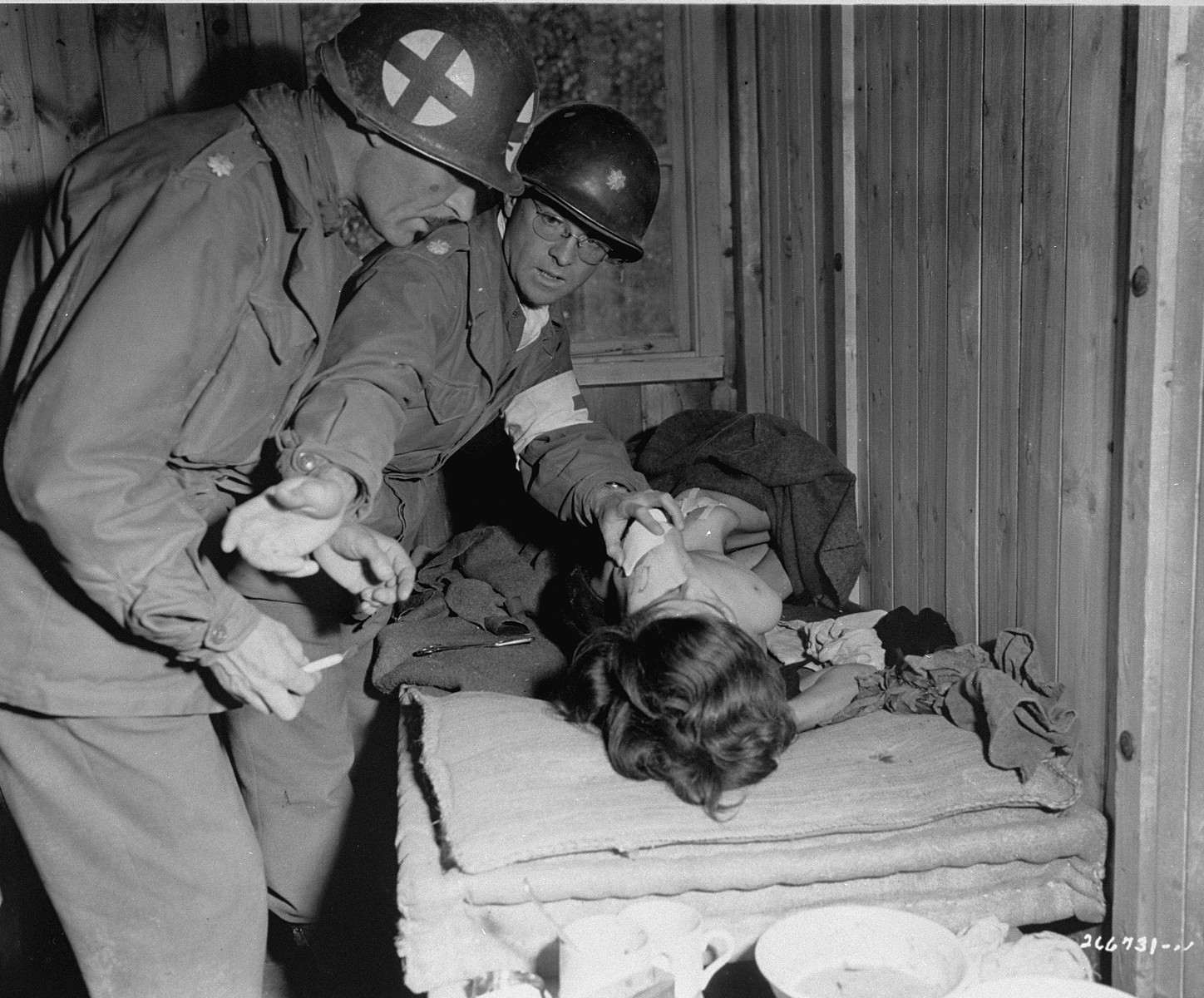 Lt. Col. J. W. Branch, Chief Surgeon of the 6th Armored Division, 3rd U.S. Army, treats the wounds of a Hungarian Jewish woman in Penig, a sub-camp of Buchenwald.